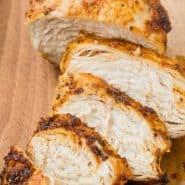 "Cut chicken on a cutting board, text overlay reads ""air fryer chicken breasts, rachelcooks.com"""