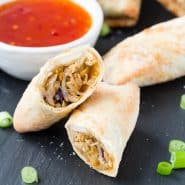 Cut open egg roll on black surface, dipping sauce in background.