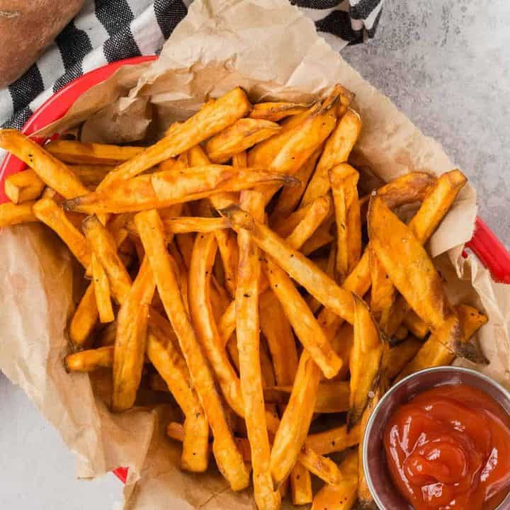 Red basket full of air fryer sweet potato fries, with a small container of ketchup