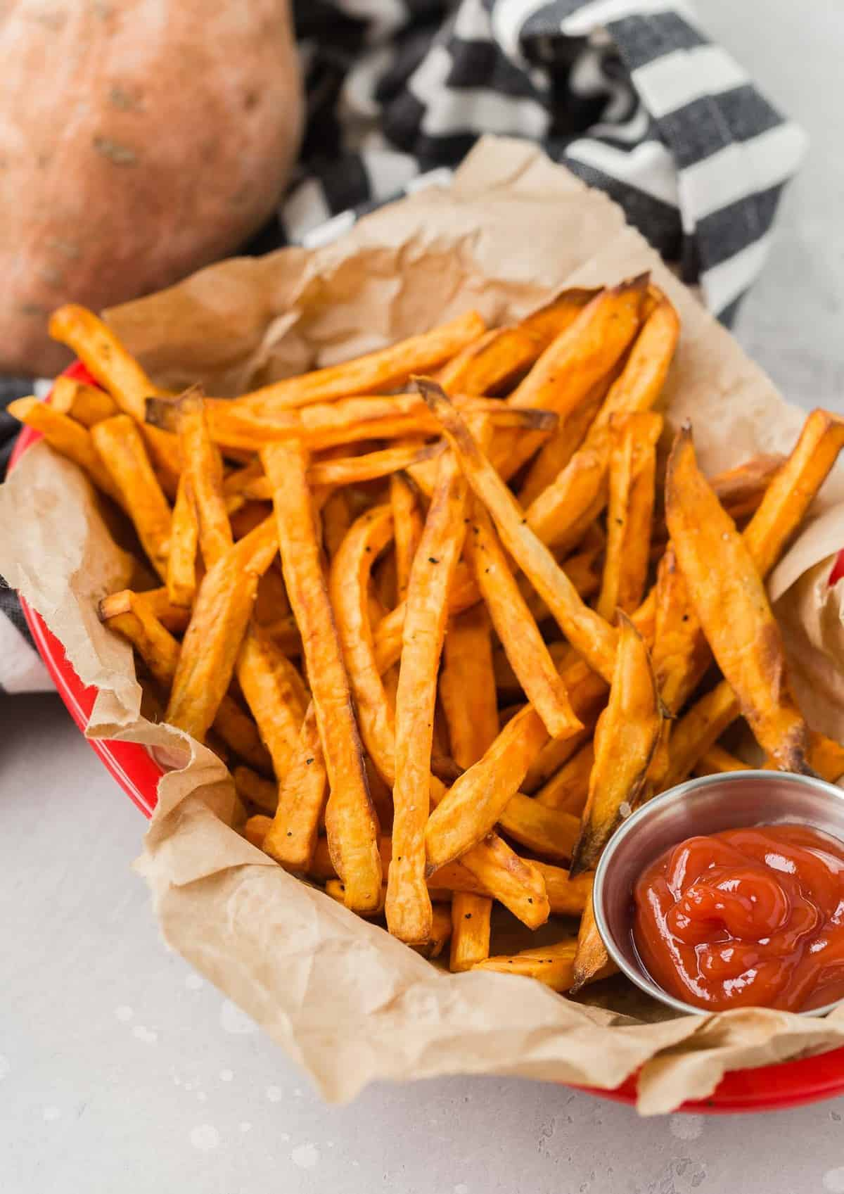 Overhead view of sweet potato fries in a brown paper lined basket with a small cup of ketchup.
