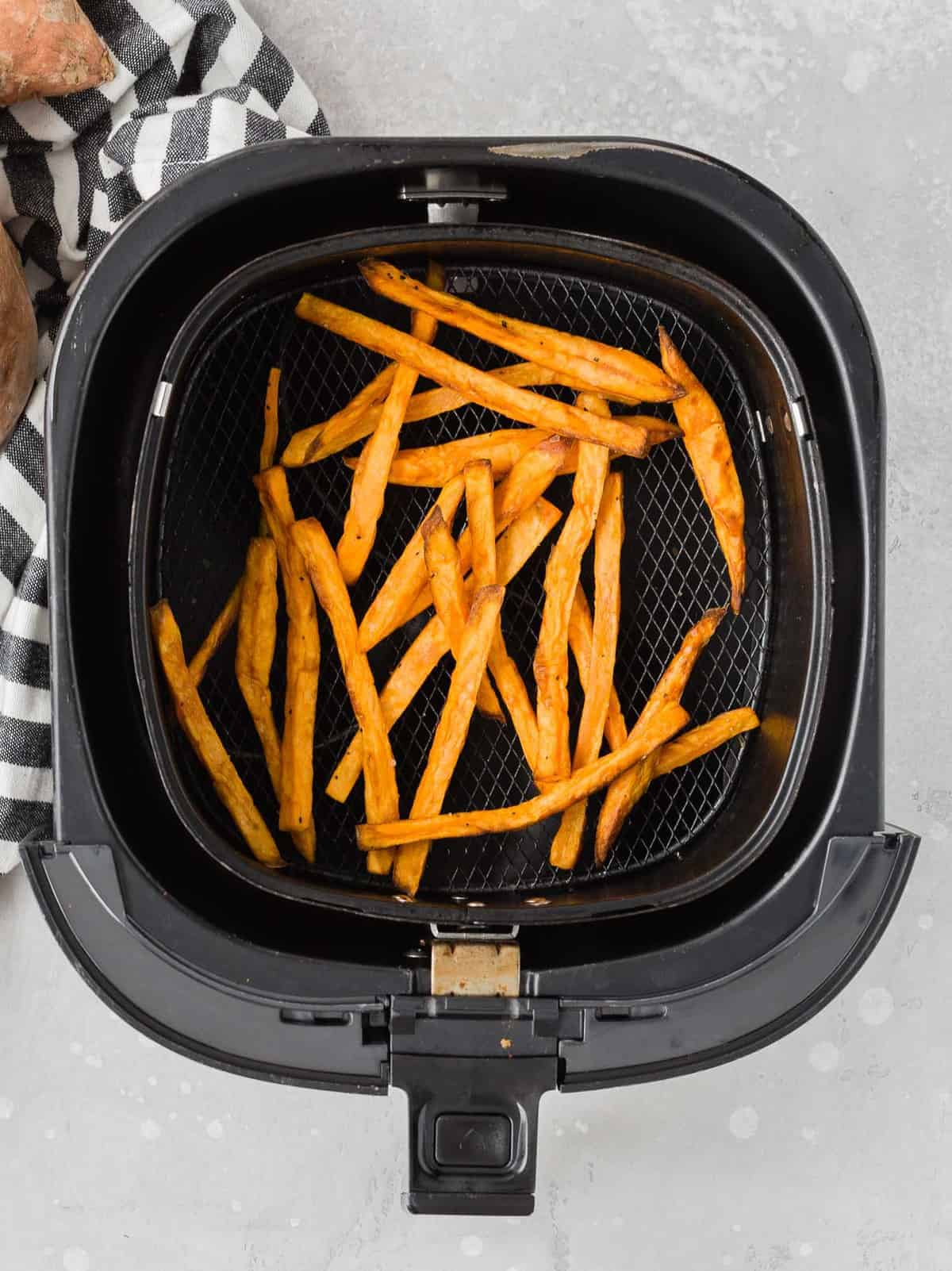 Overhead view of cooked sweet potato fries in an air fryer.