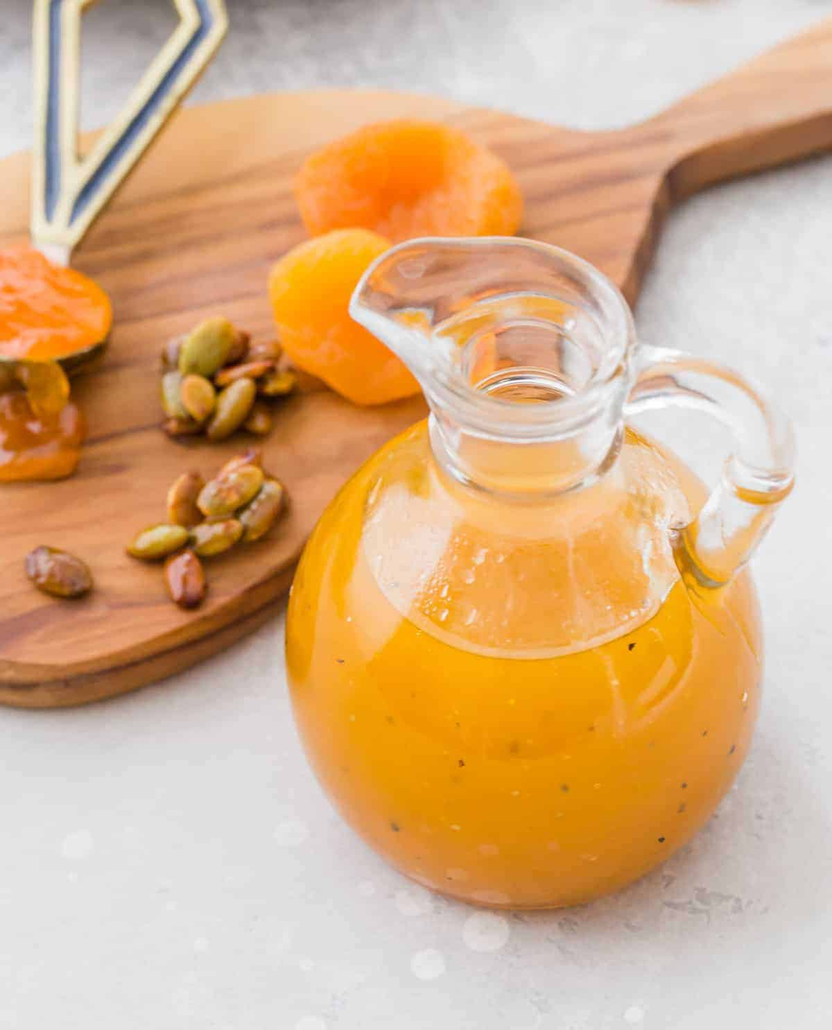 Dressing in a glass bottle, apricots and pepitas in the background.