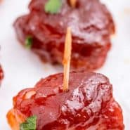 """Close up of an appetizer on a toothpick, text overlay reads """"bacon wrapped water chestnuts"""""""
