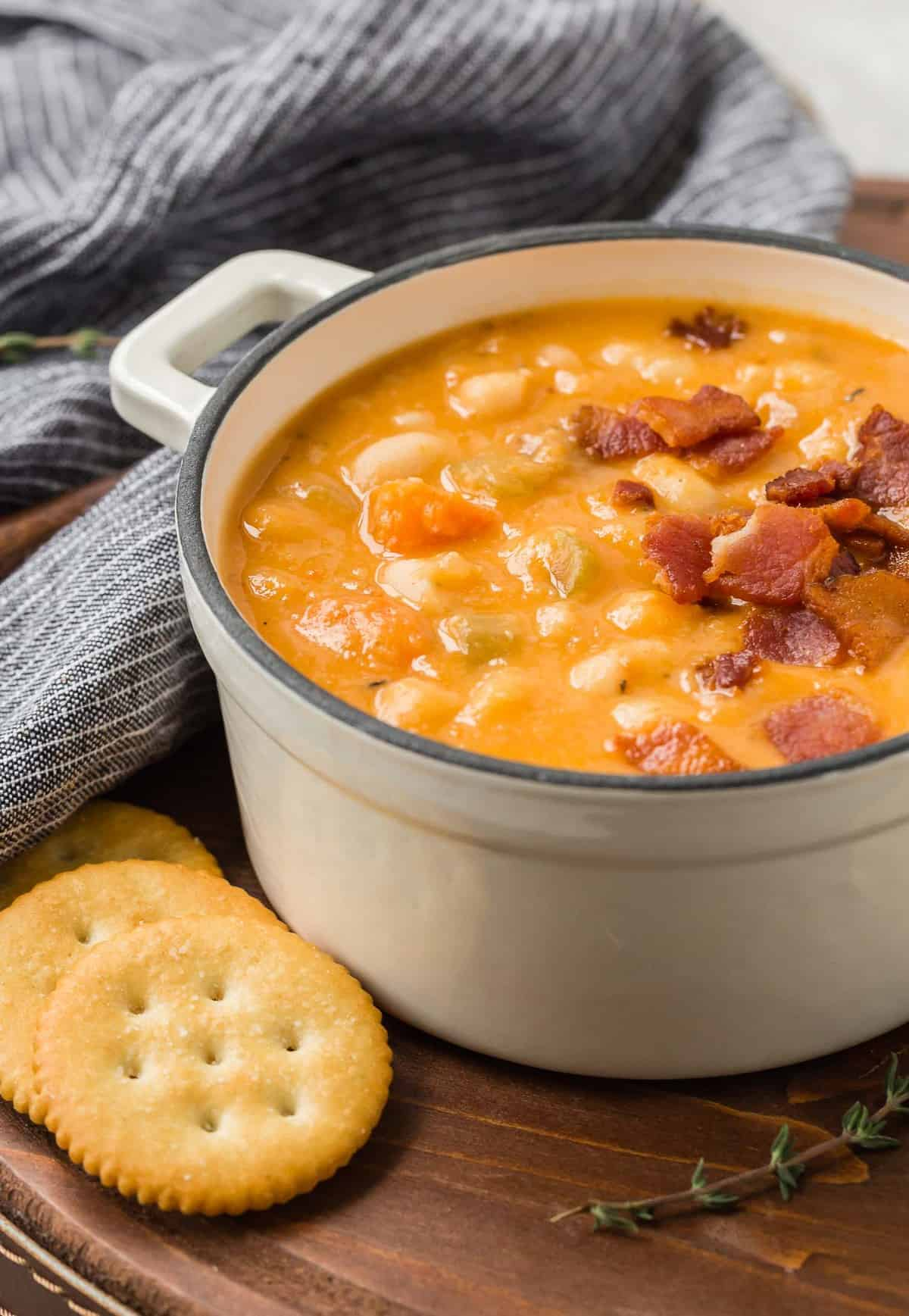 Bean soup on a tray with crackers and fresh thyme.
