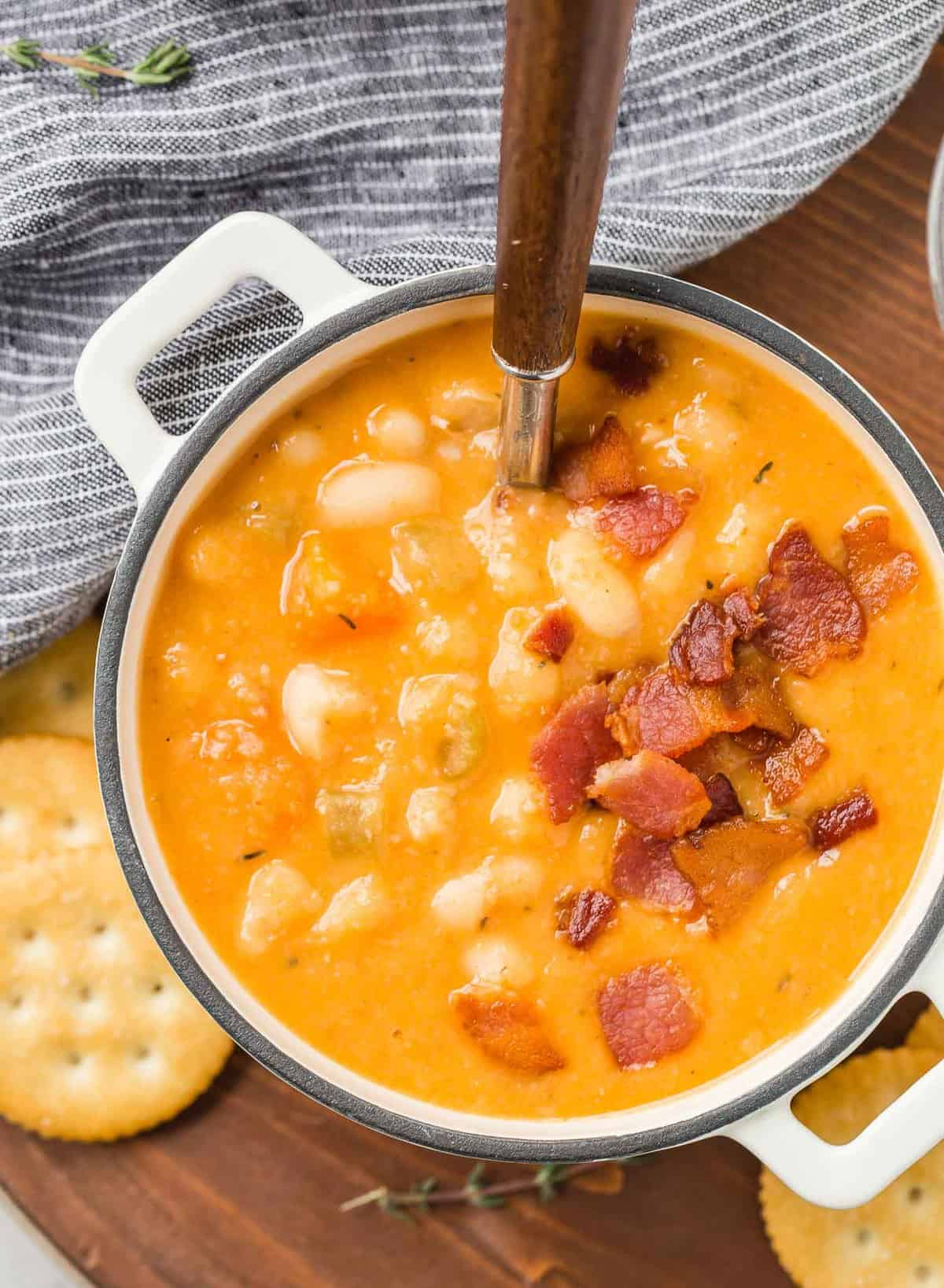 Overhead view of orange colored bean soup topped with crumbled bacon.