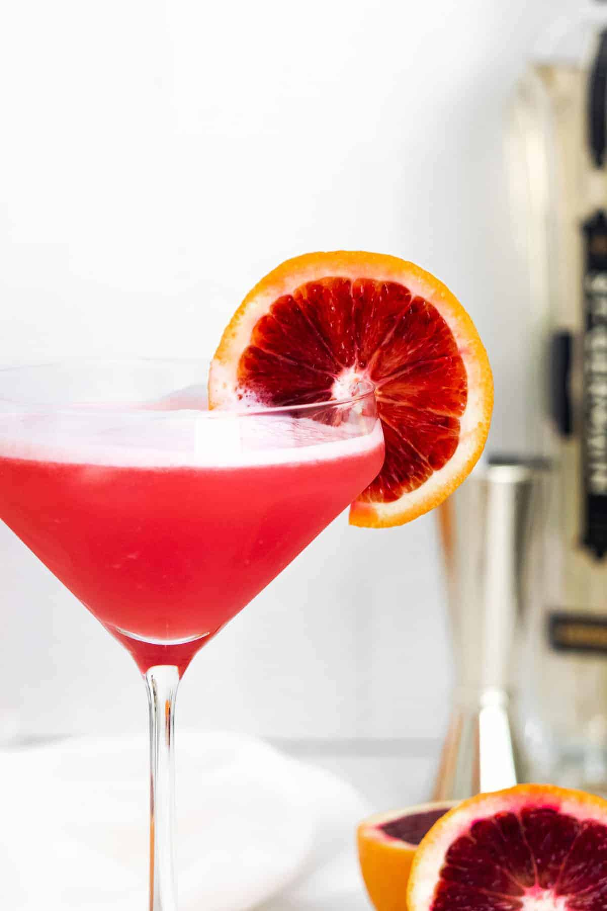 Close up of bright red cocktail garnished with blood orange.