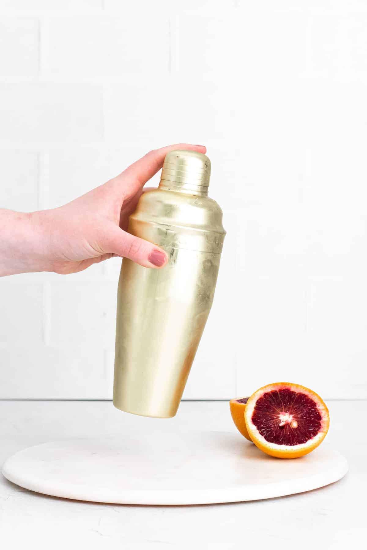 Gold cocktail shaker being shaken.