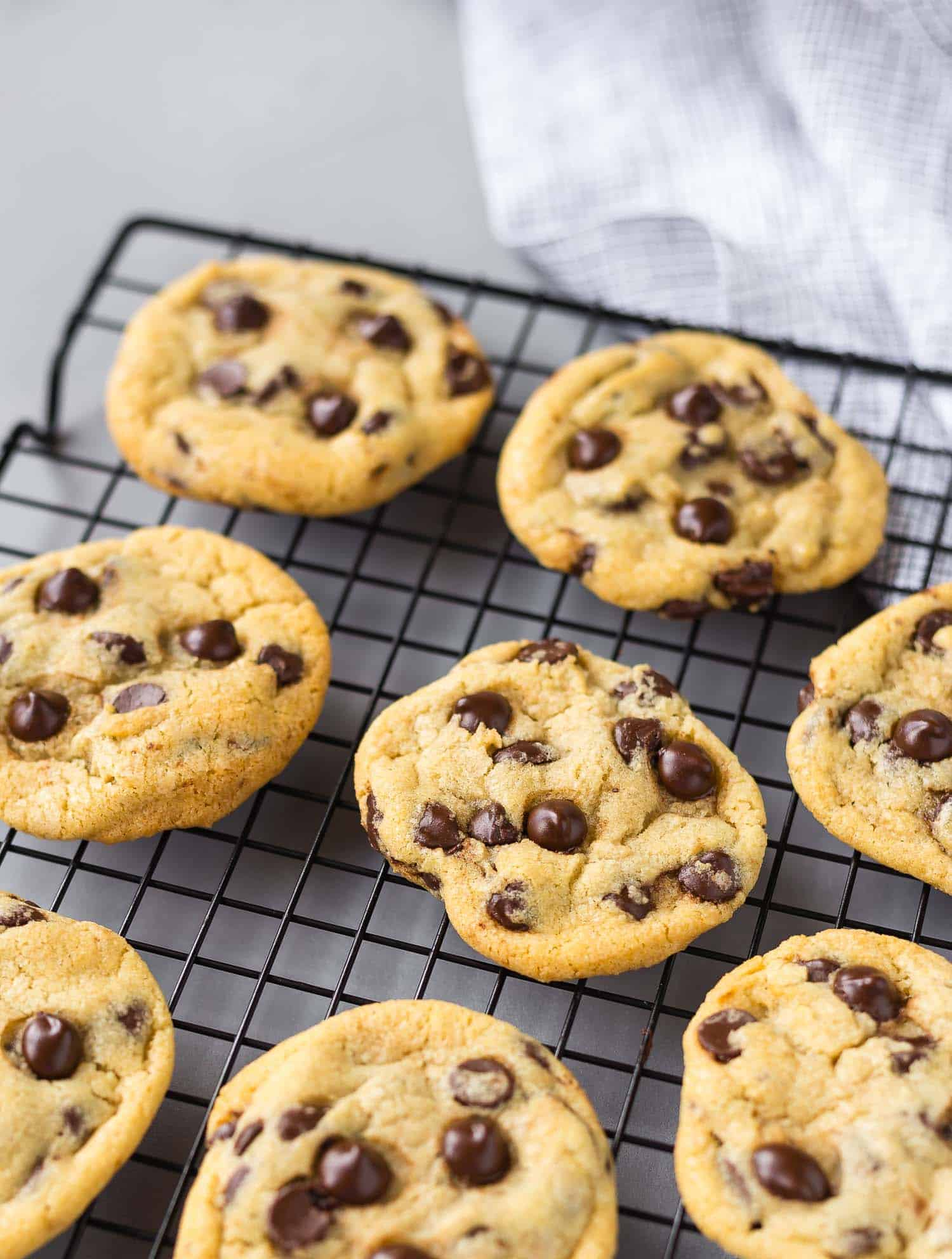 Cookies studded with chocolate chips on a cooling rack.