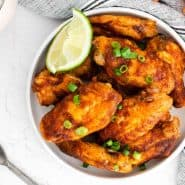 Glazed wings in a white dish with lime wedges.