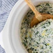 "Spinach dip in a black dish, text overlay reads ""crockpot spinach artichoke dip, rachelcooks.com"""