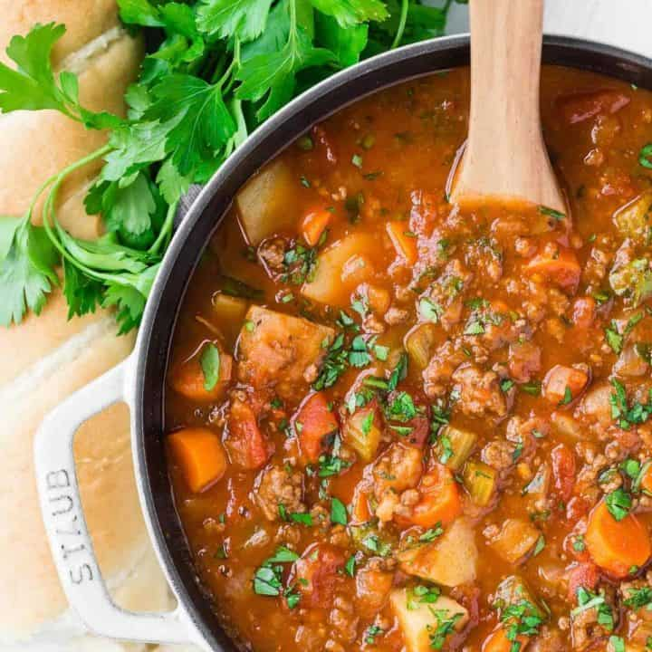 Overhead view of hamburger soup with potatoes, tomatoes, and vegetables.
