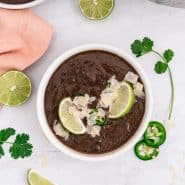 Overhead view of a bowl of black bean soup garnished with lime slices and jalapeno.