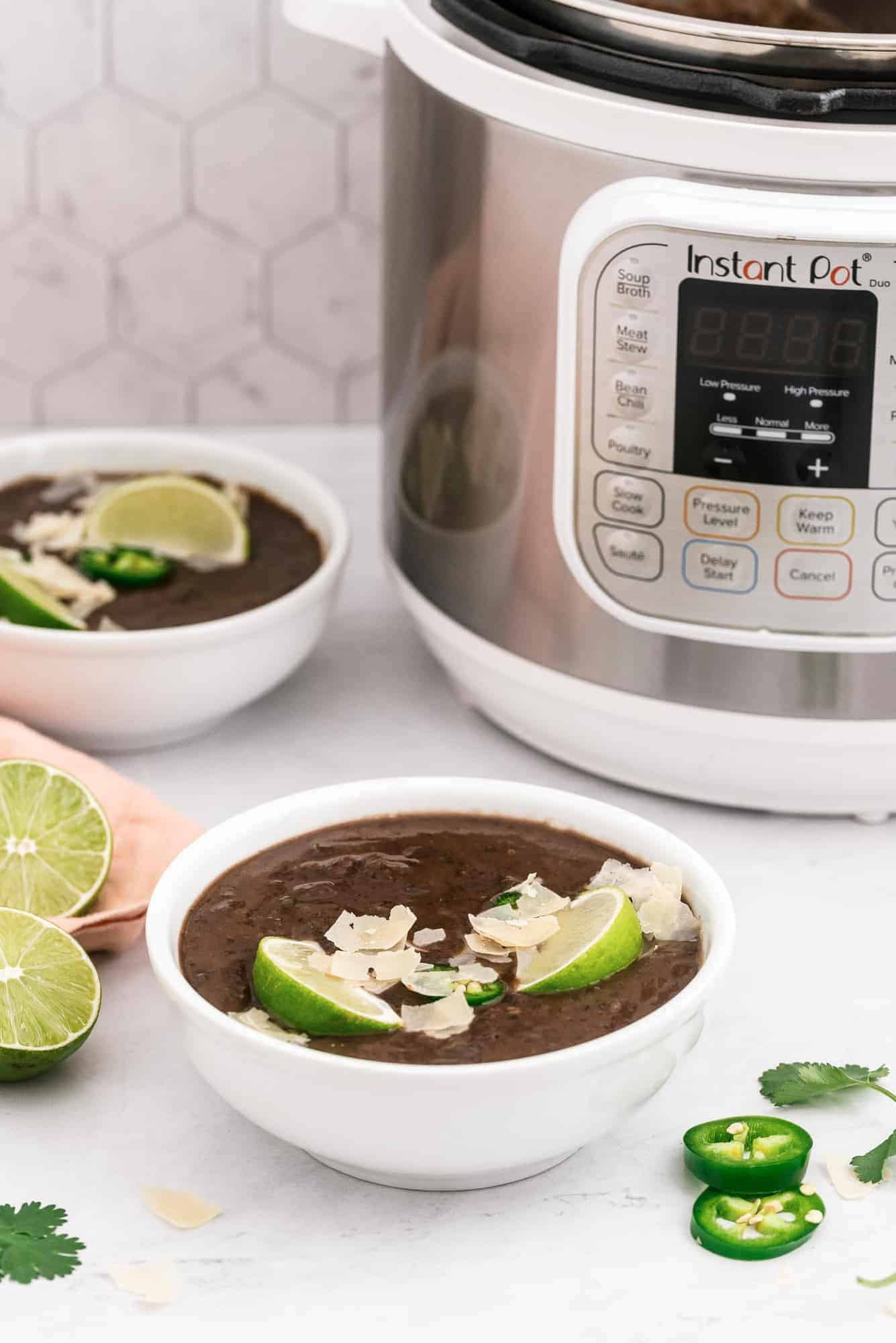 Two bowls of soup in front of an instant pot.