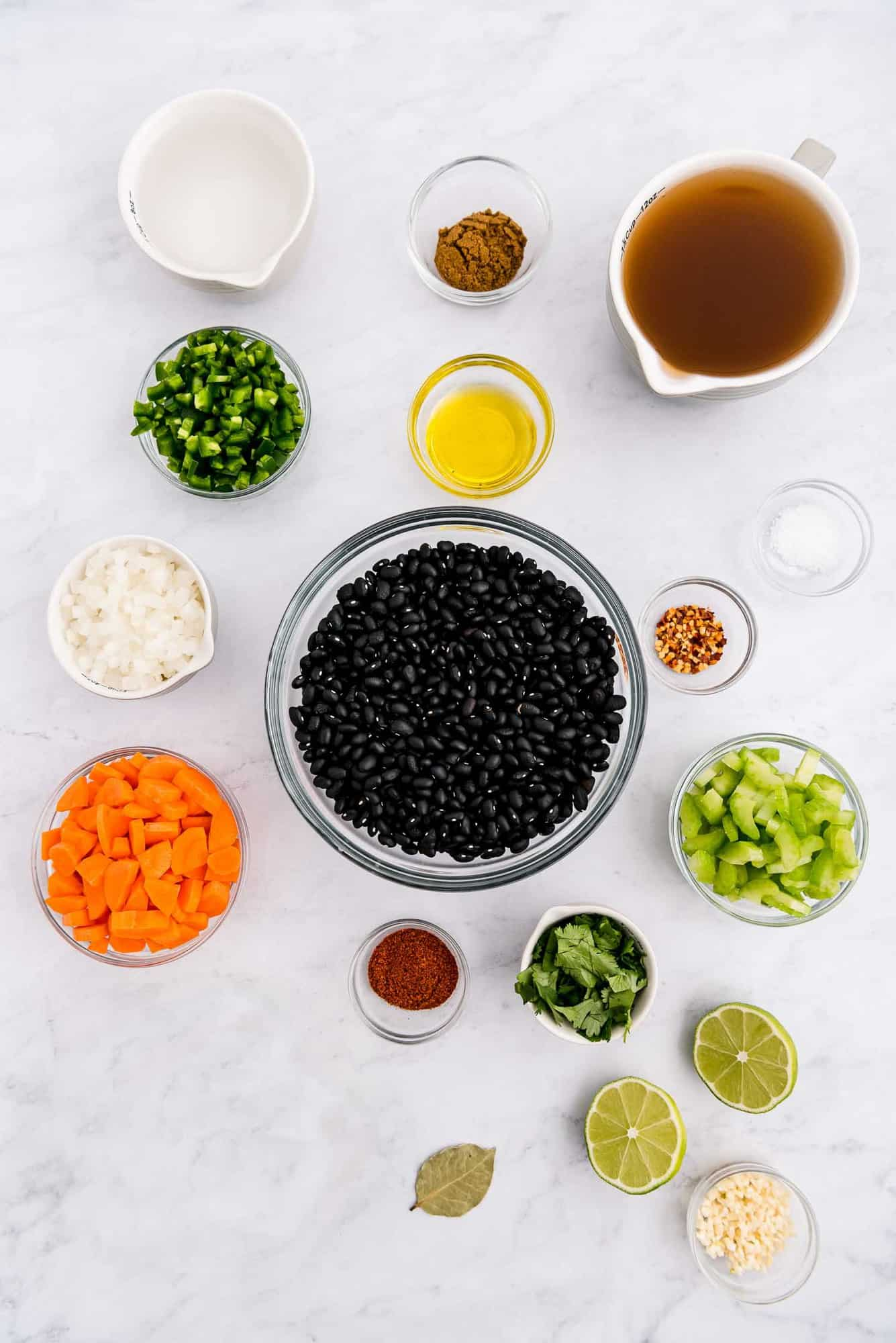 Overhead view of colorful ingredients in glass bowls, including black beans, carrots, jalapeno, and more.