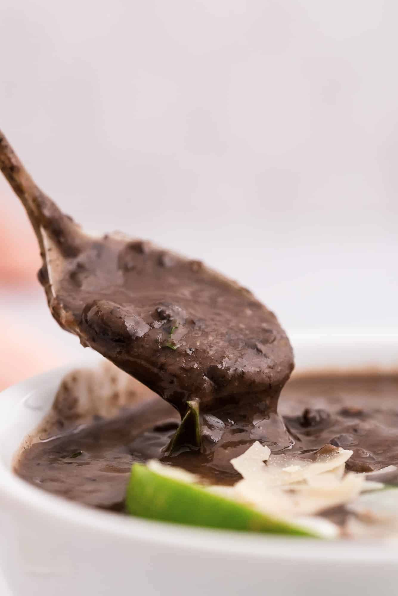 Black bean soup on a spoon, being pulled out of a bowl.