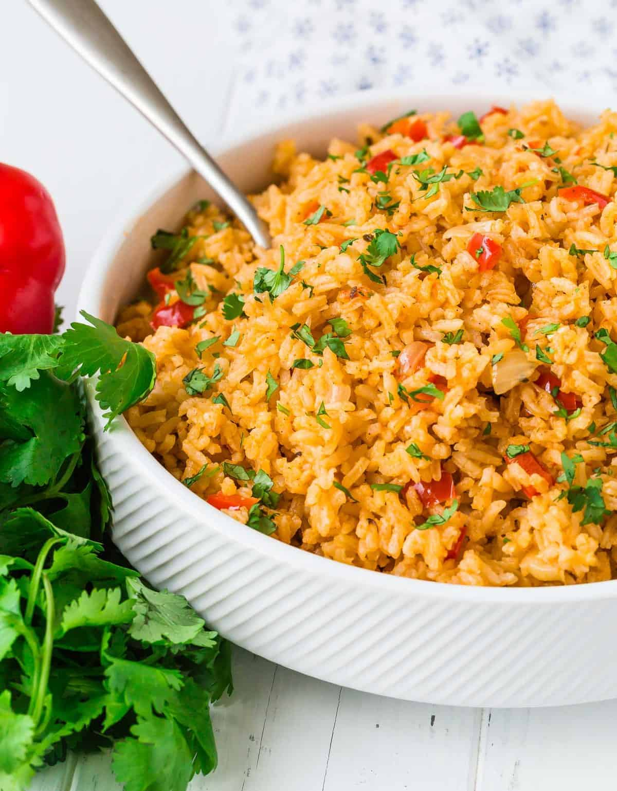 Mexican rice in a white bowl with a silver serving spoon.