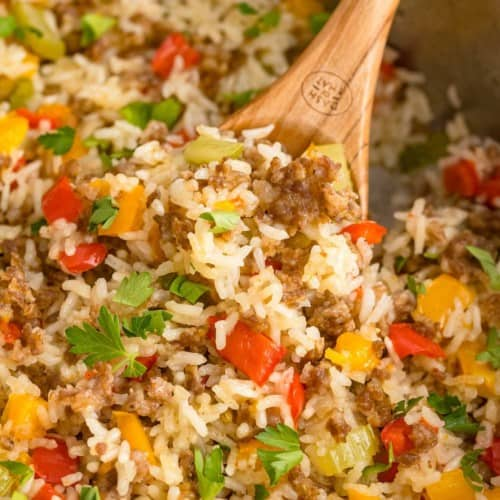 Close up of sausage, rice, and bell peppers in a skillet with a wooden spoon.