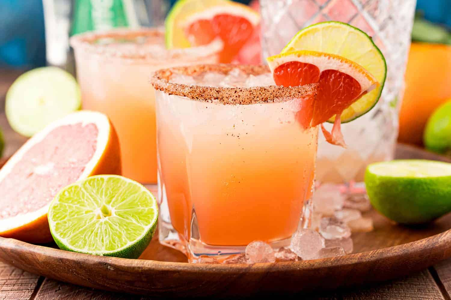 Light orange-pink cocktails on a wooden tray with ice, limes, grapefruits.