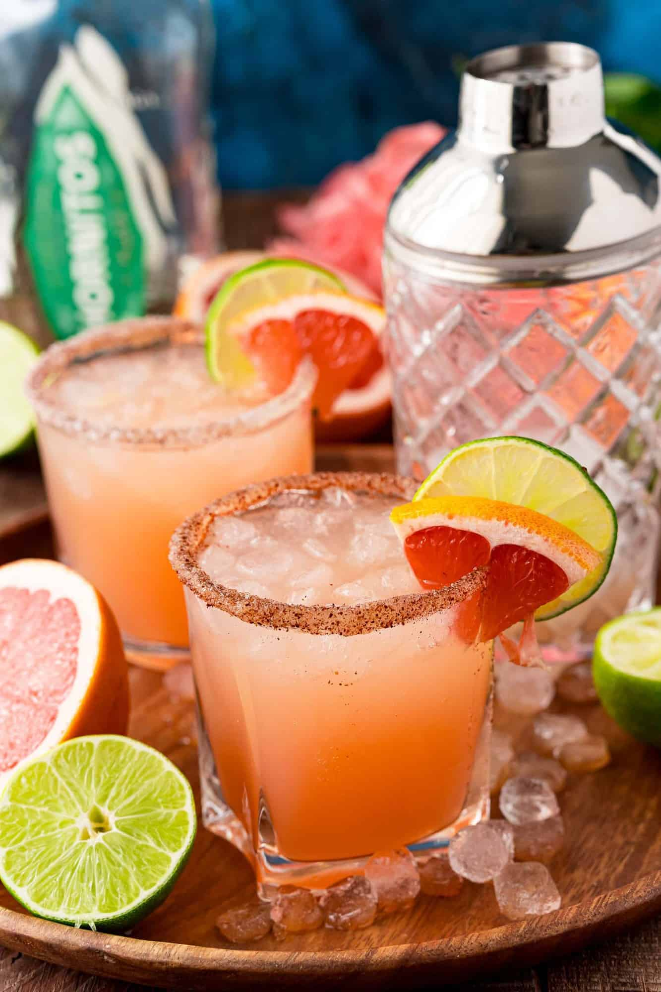 Two light pink cocktails on ice, garnished with grapefruit and lime.