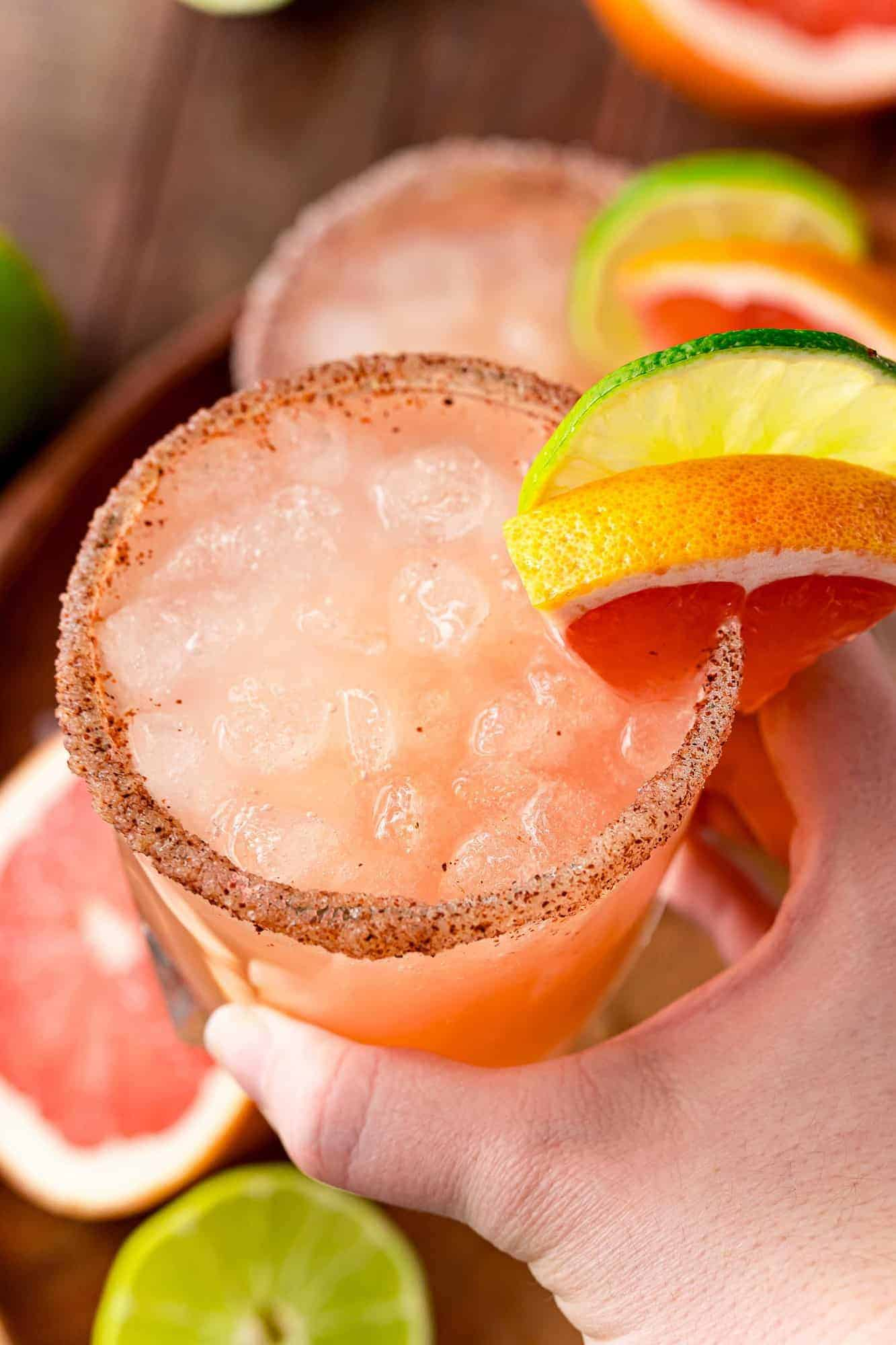 Grapefruit cocktail on ice, being held in a hand.