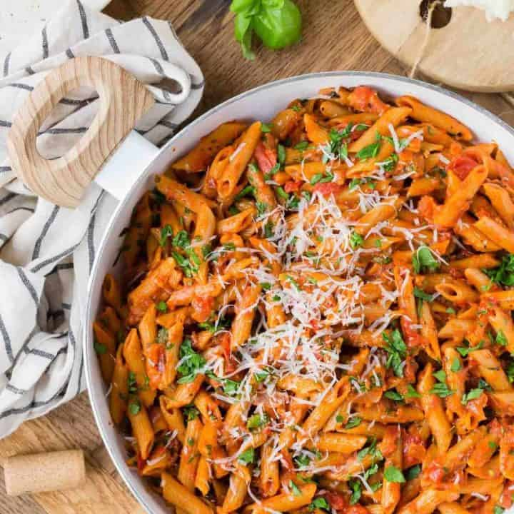 Overhead view of a pan of pasta with tomato sauce, fresh parsley, and grated cheese.
