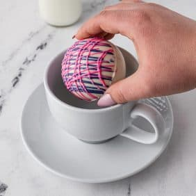 A hot cocoa bomb being added to a white mug on a saucer.