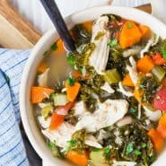 Colorful bowl of soup with chicken, kale, carrots.