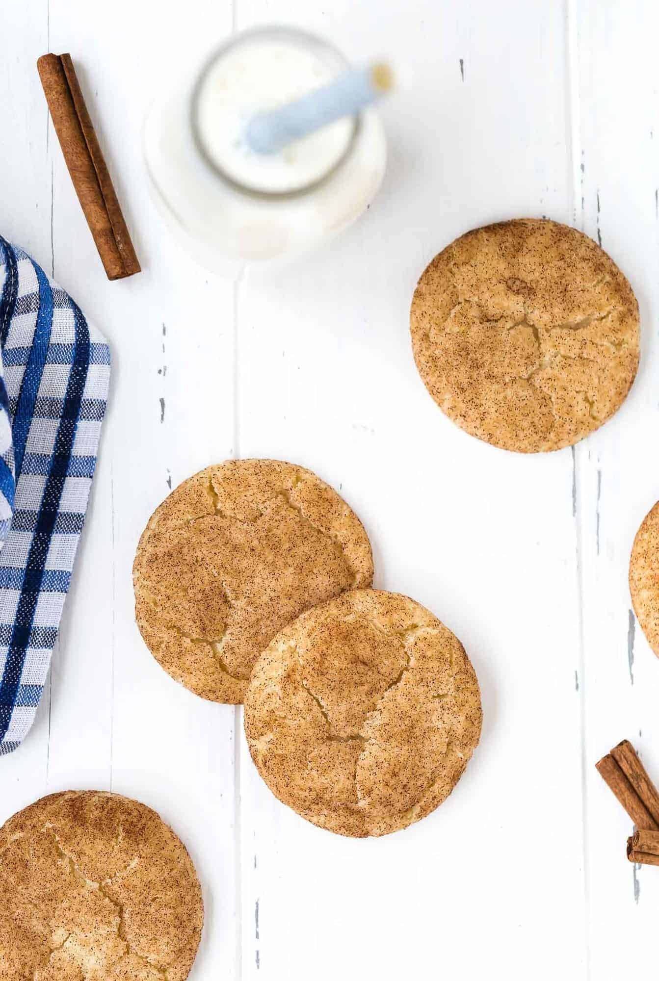 Overhead view of cinnamon cookies on a white surface with cinnamon sticks and milk.