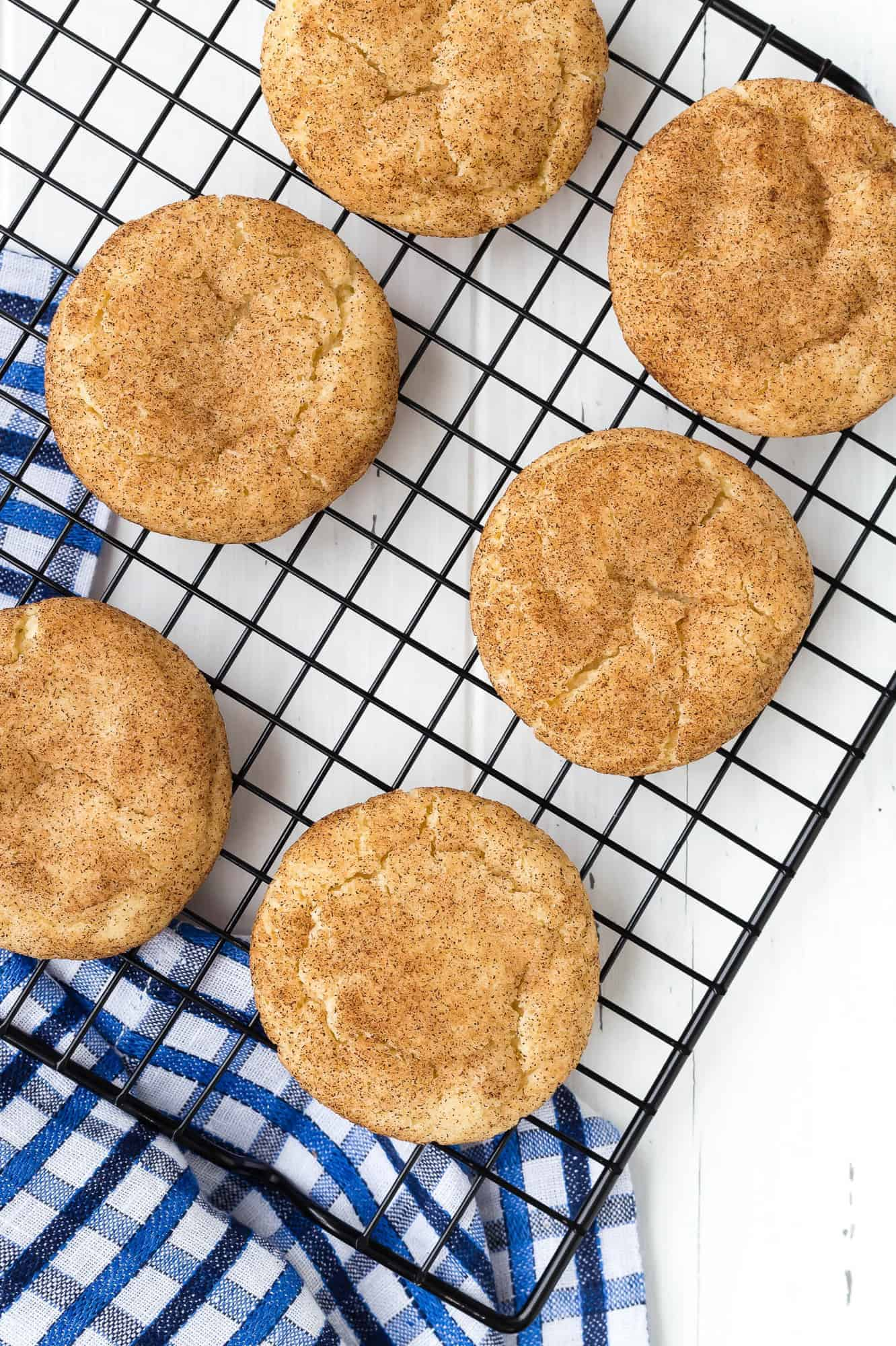 Overhead view of snickerdoodles on a cooling rack with a blue and white towel underneath.