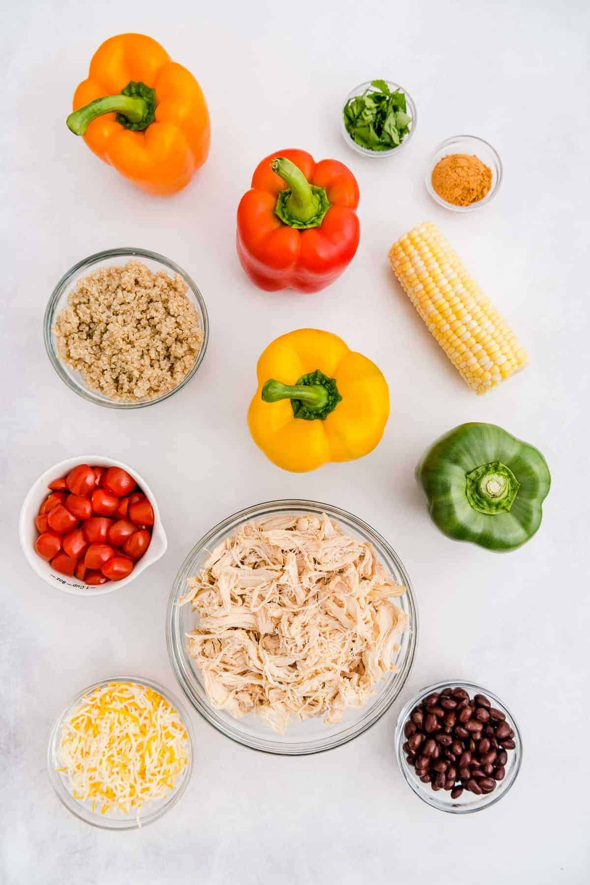 Overhead view of ingredients needed to make stuffed peppers: peppers, chicken, beans, and more.