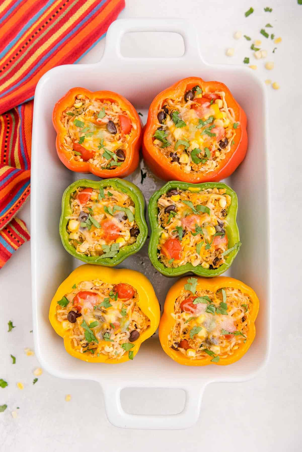 Overhead view of six stuffed peppers in a white glass pan.