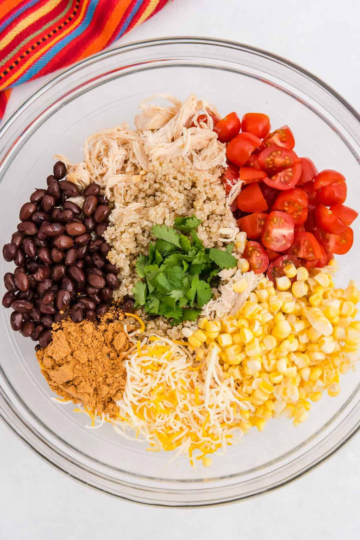 Colorful ingredients in a glass bowl: quinoa, chicken, black beans, tomatoes, and more.