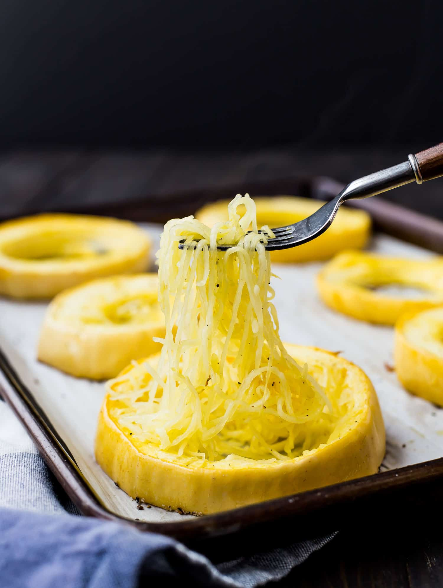 Ring of spaghetti squash, strands being pulled out with a fork.