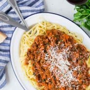 Overhead view of large platter with linguine and turkey bolognese, topped with cheese.