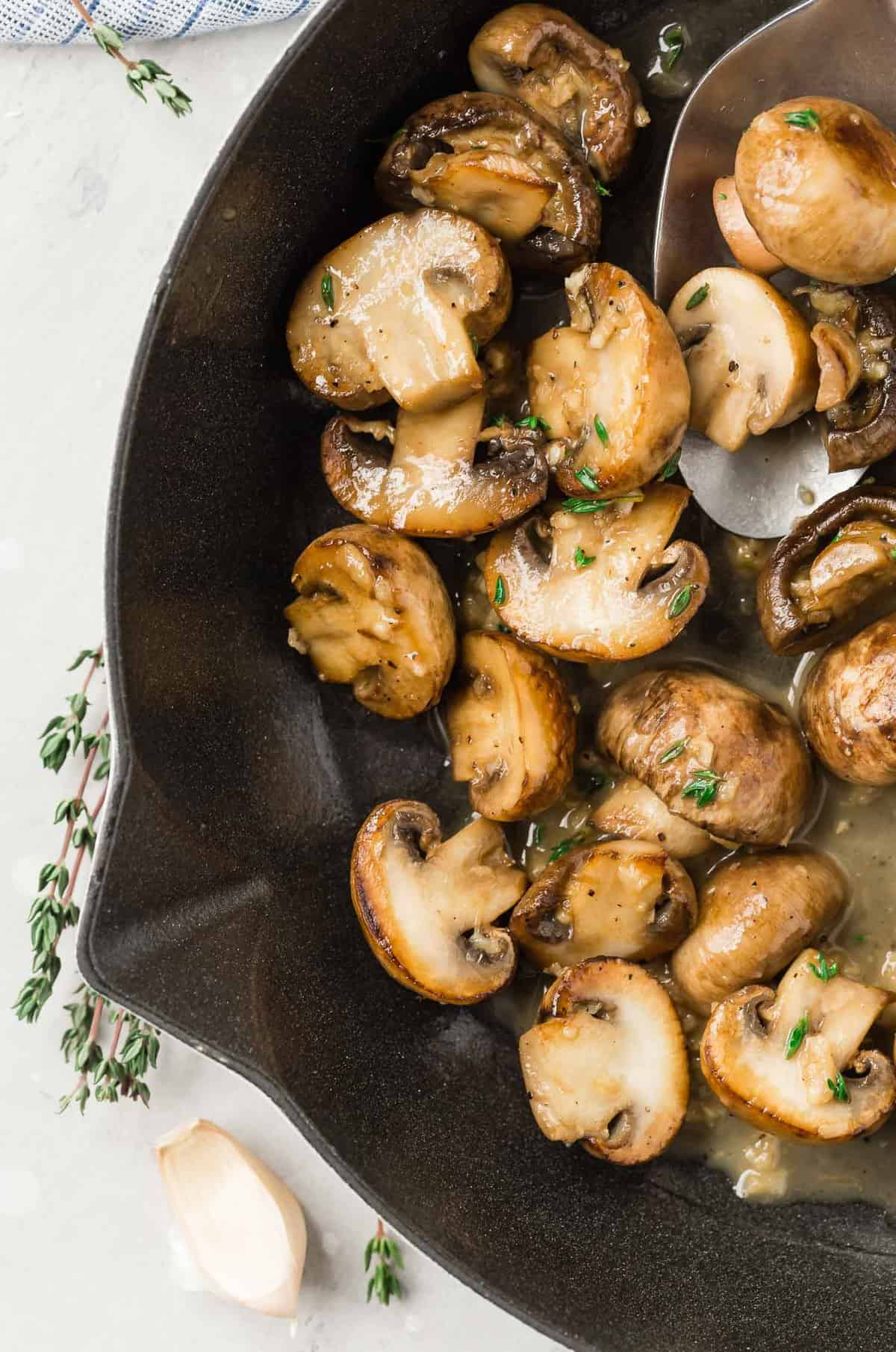 Mushrooms in a white wine sauce in a pan, with fresh thyme.