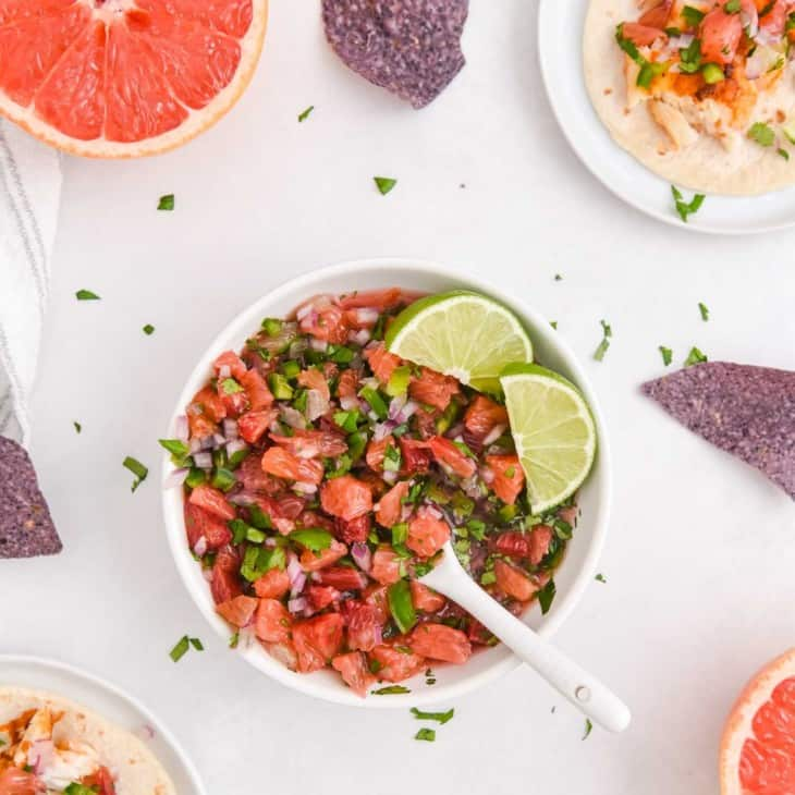 Colorful salsa with oranges and grapefruit in a bowl with a spoon and lime wedges.
