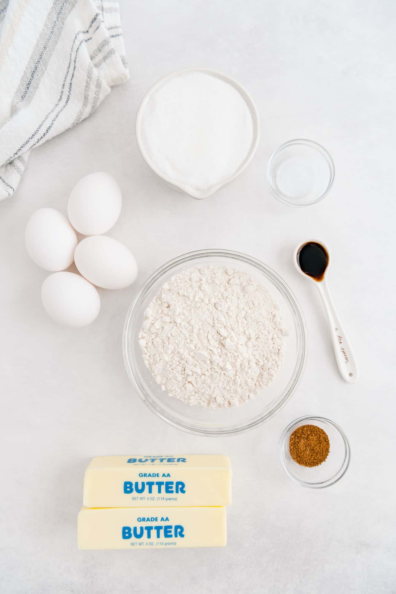Overhead view of ingredients: butter, eggs, flour, sugar, vanilla, and nutmeg.