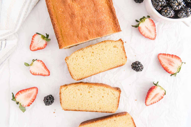 Cake, sliced. Fresh strawberries scattered around.