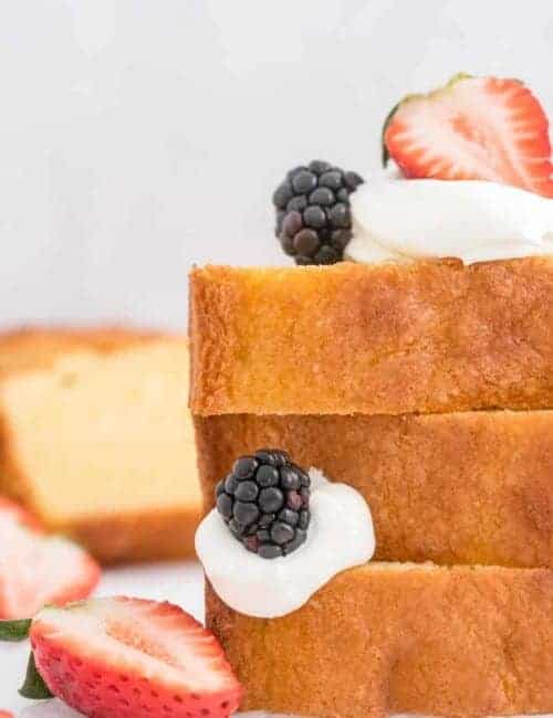 Stacked slices of cake with fruit and whipped cream.