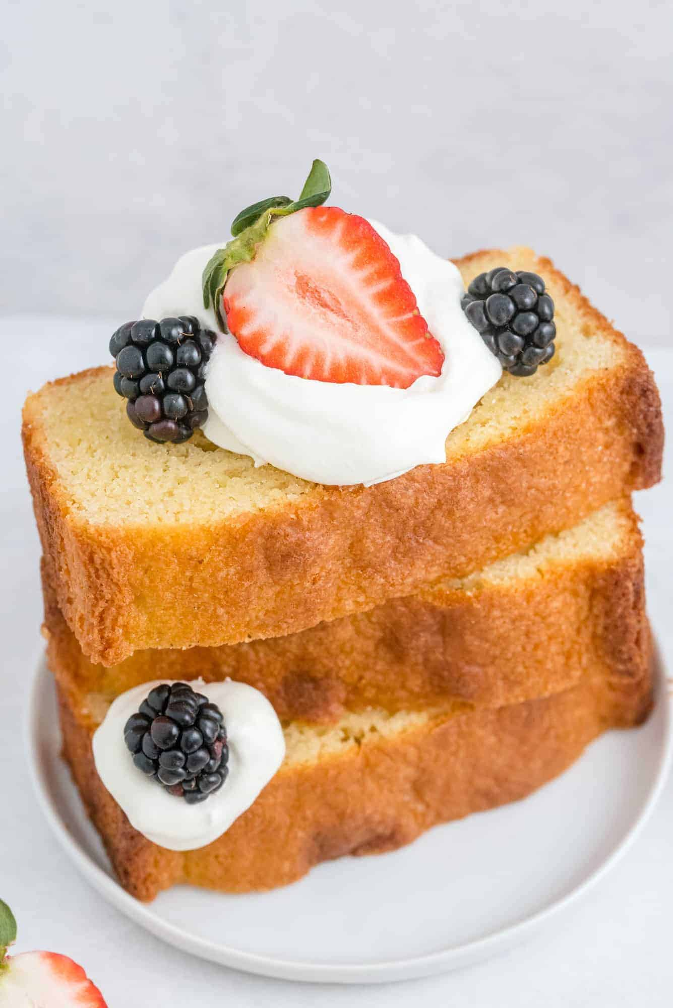 Pound cake slices stacked with fruit and berries.