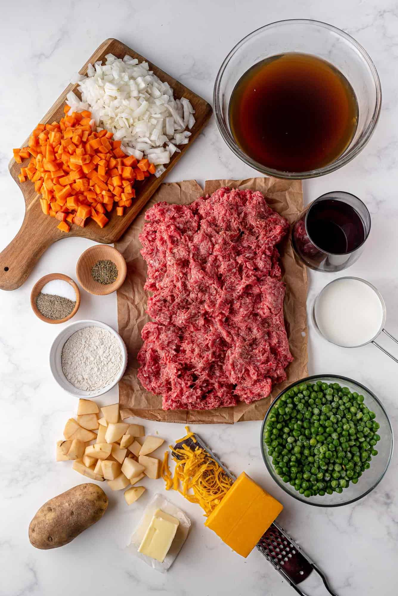 Overhead view of ingredients: Ground meat, vegetables, wine, cheese, potatoes, and seasoning.