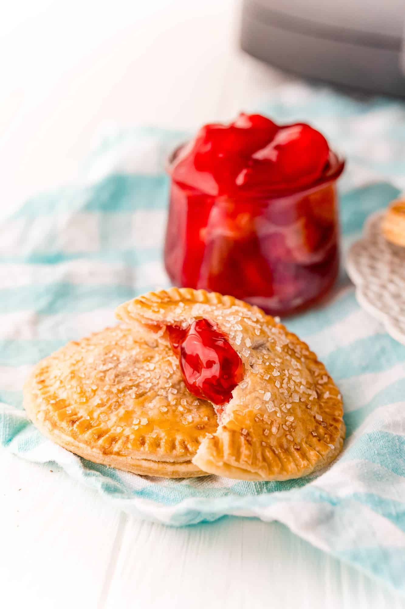 Two hand pies, one with a bite out of it to show cherry pie filling.