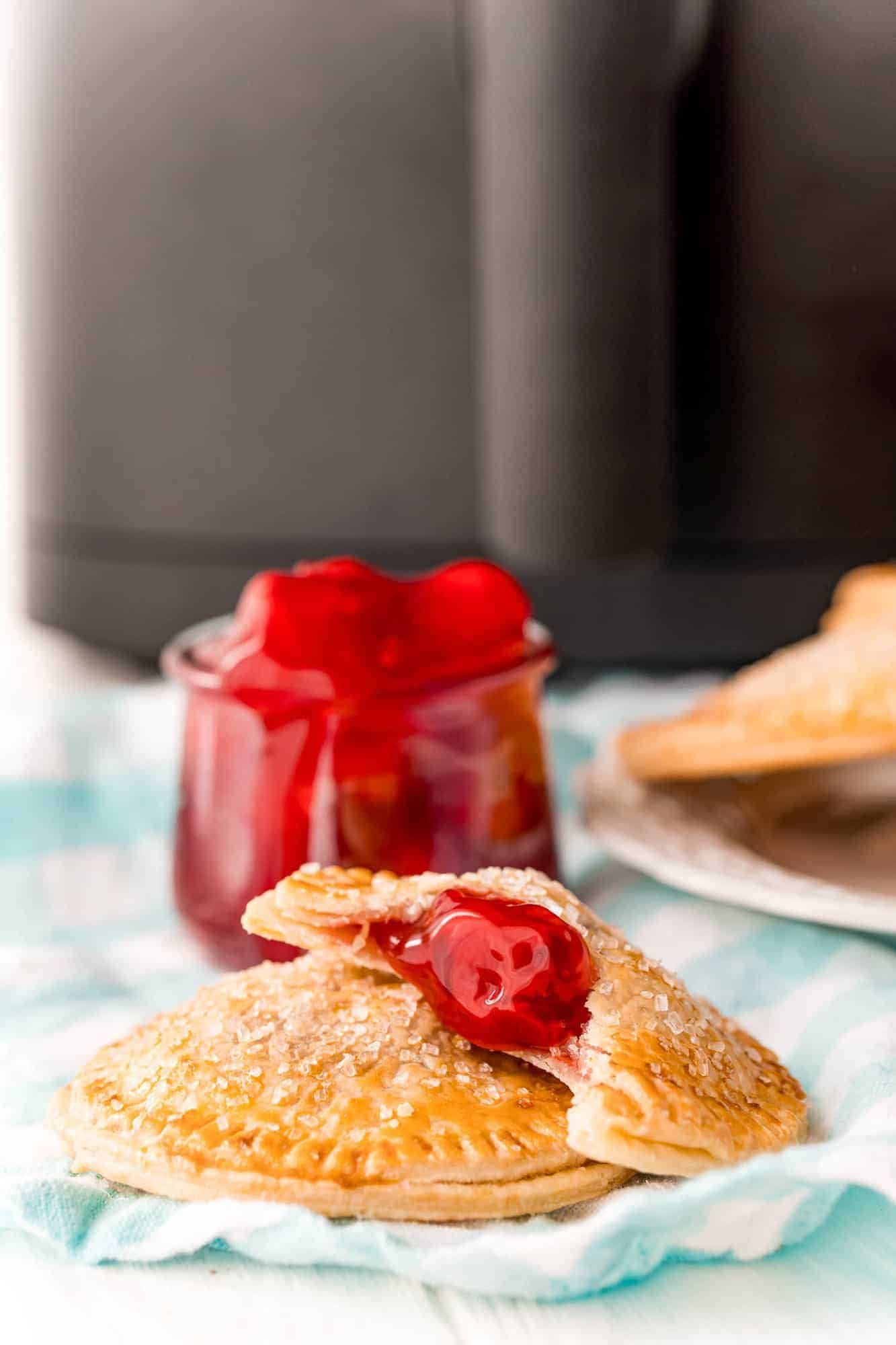 Cherry hand pies in front of an air fryer.