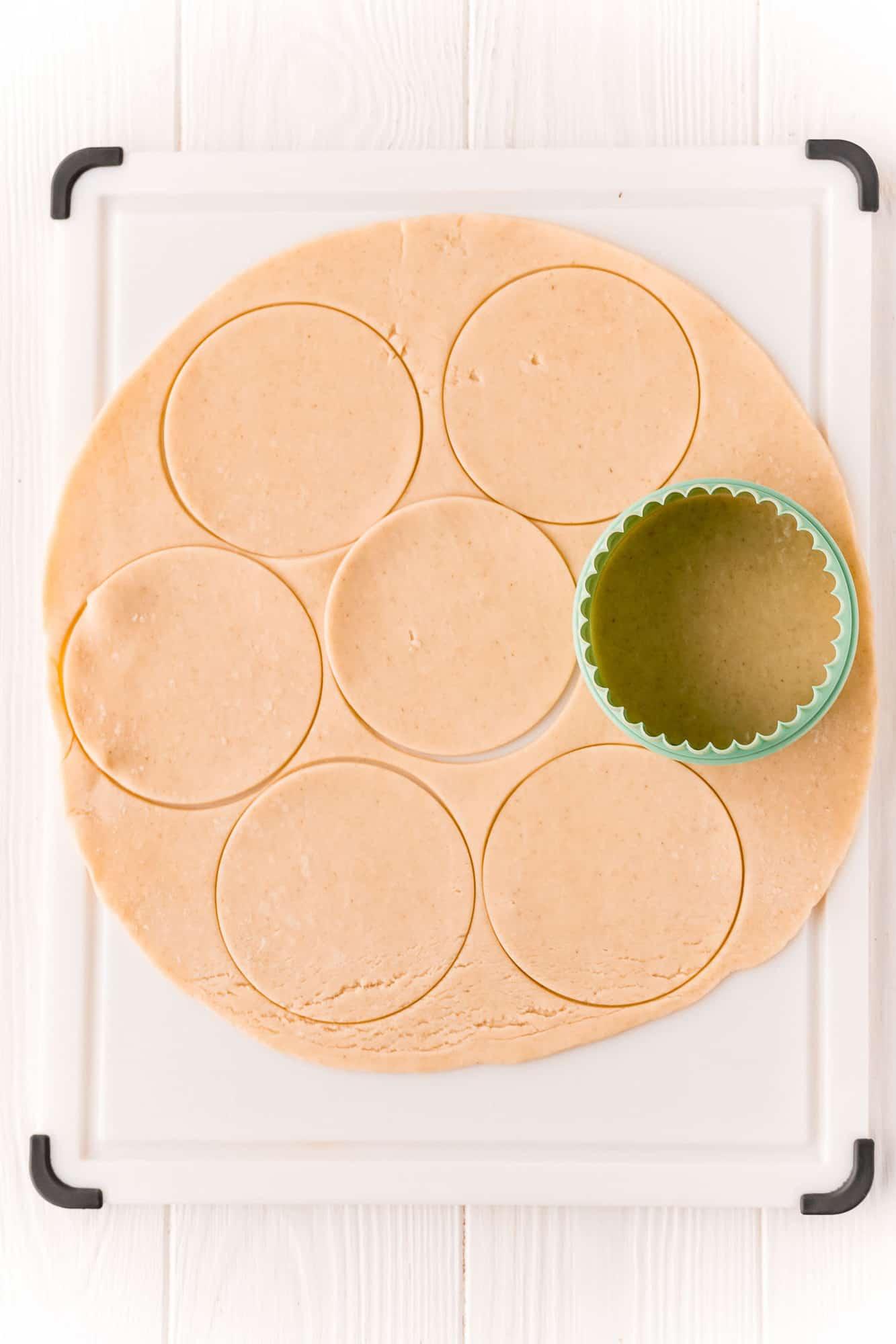 Biscuit cutter cutting a pie crust into circles.