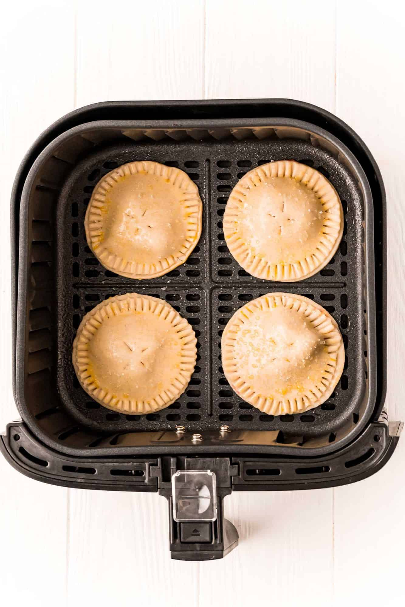 Uncooked hand pies in the basket of an air fryer.
