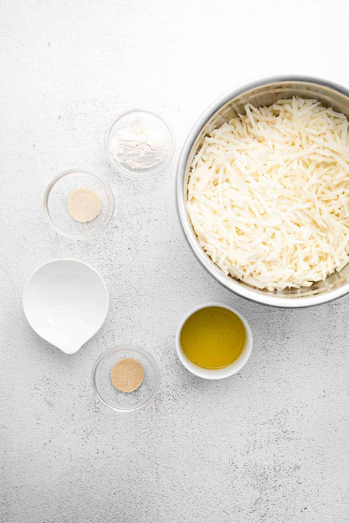 Overhead view of ingredients: shredded potatoes, olive oil, flour, and spices.
