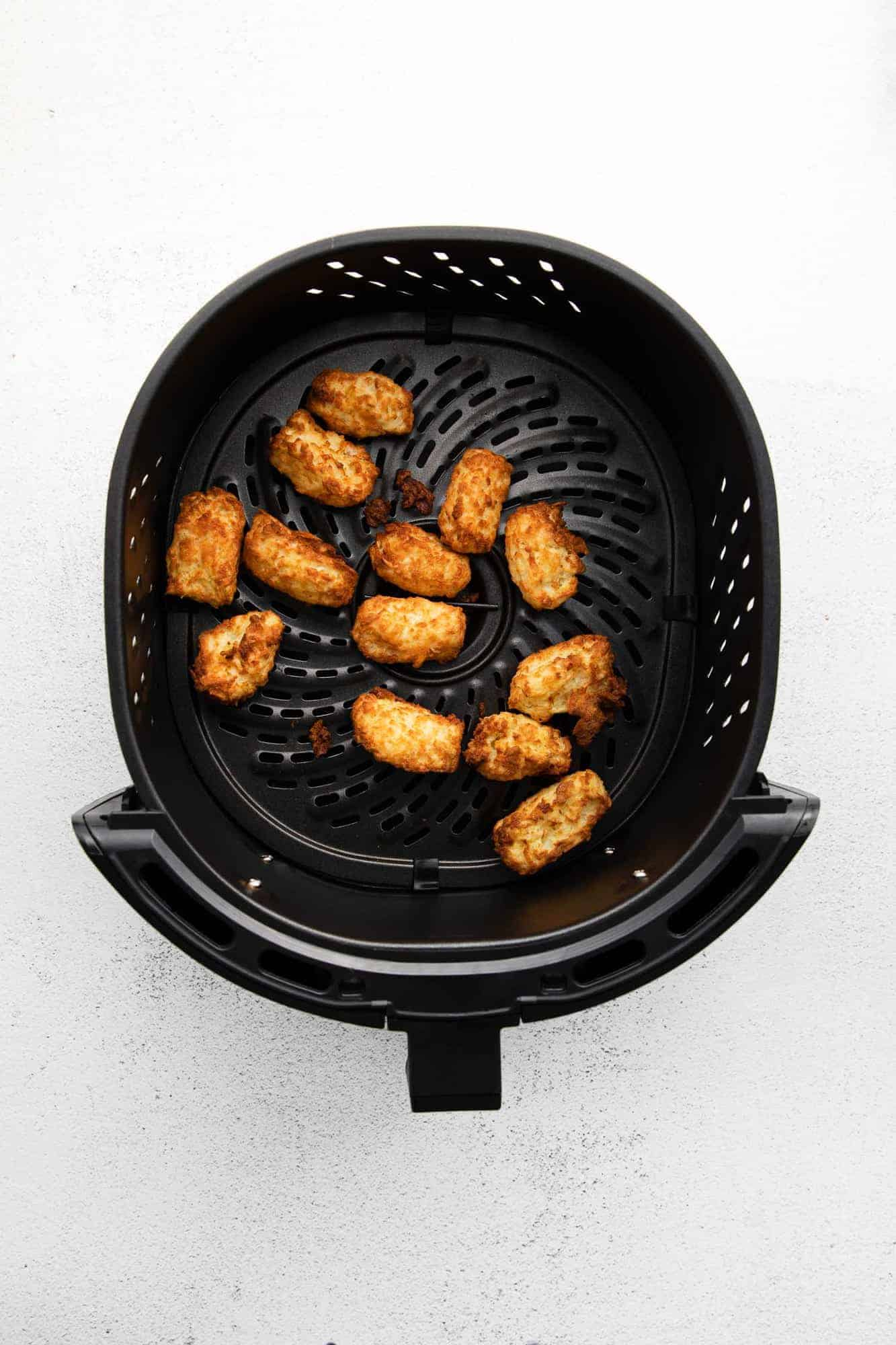 Cooked air fryer tater tots still in basket.