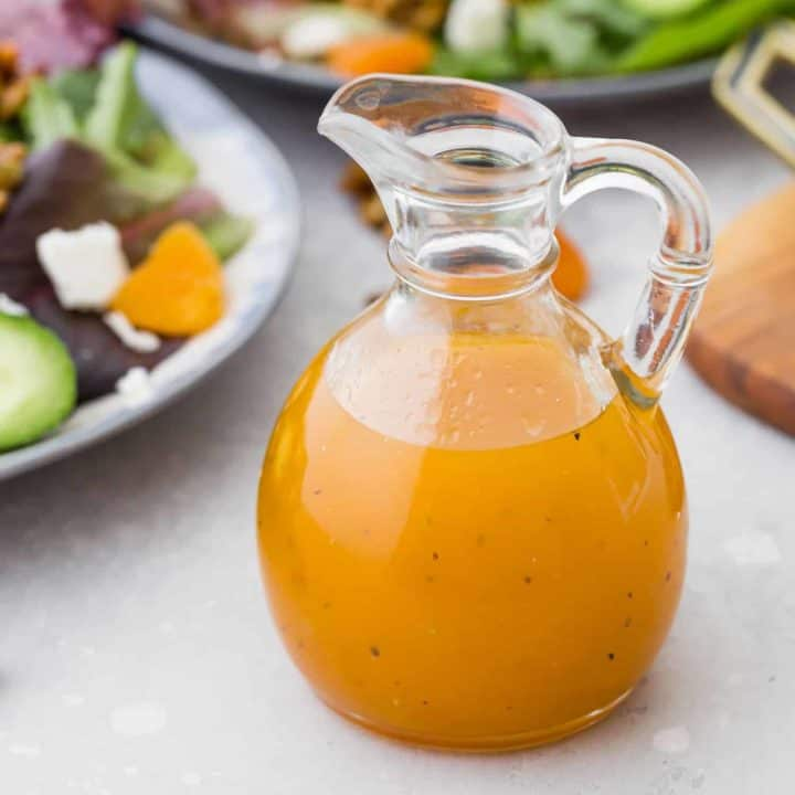 Bright orange salad dressing in a jar in front of salads.