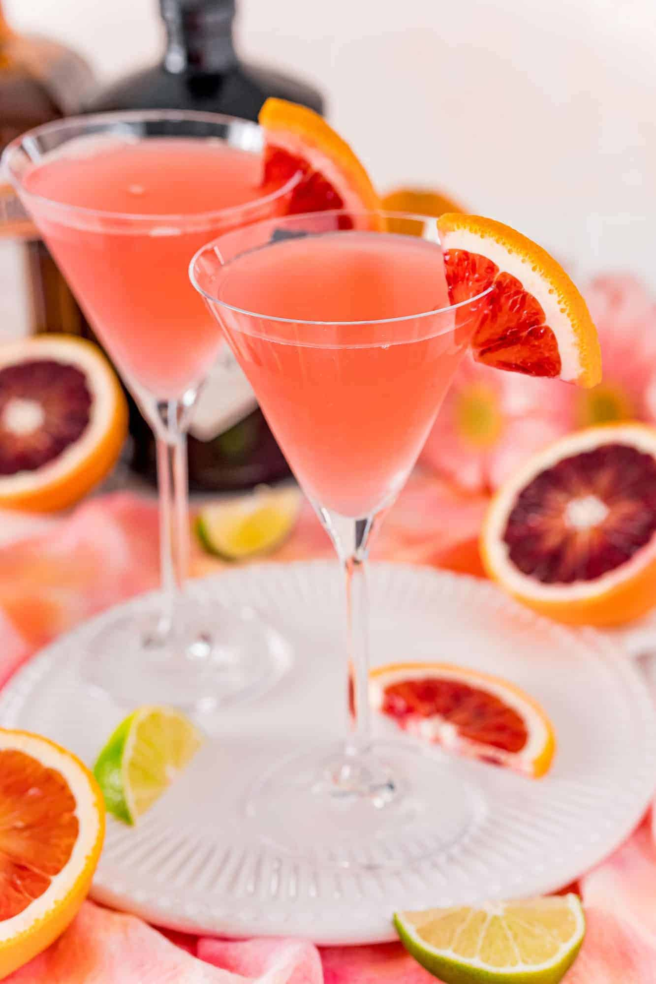 Two light red martinis on a white tray.