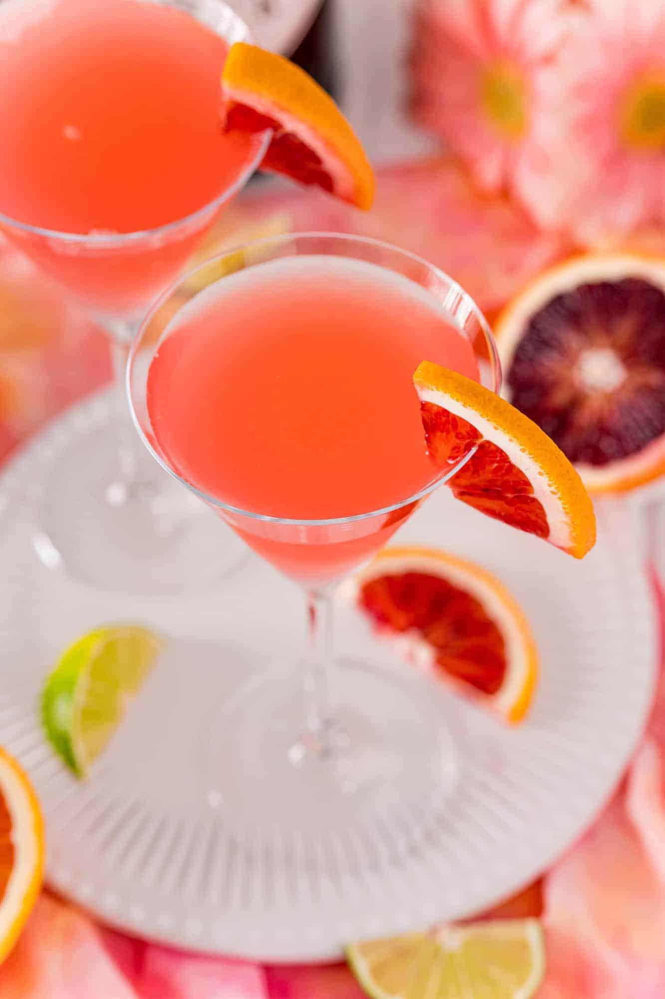Blood orange martini on a white tray, garnished with orange wedges.